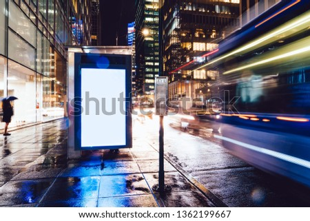 Bus station billboard in rainy night with blank copy space screen for advertising or promotional content, empty mock up Lightbox for information, blank display in urban city street with long exposure