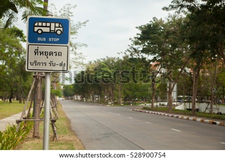 Bus stop sign in Thai and English on pole next to the road #528900754