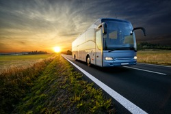 Bus traveling on the asphalt road in rural landscape at sunset