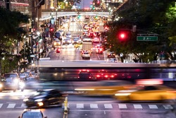 Buses and taxis driving through a busy intersection 42nd Street through Midtown Manhattan in New York City at night