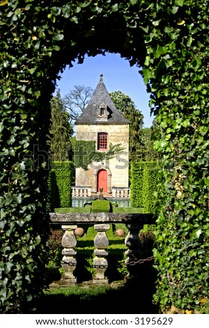 bush archway with view onto castle in the gardens of eyrignac, france