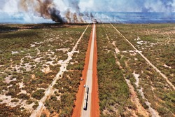 Bush Fire along the highway in Western Australia with a fuel tanker stopped on the highway