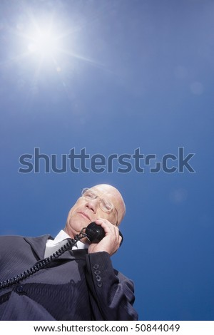 Busieness man using phone standing against sky, low angle view