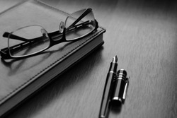 Business accessories on desktop: notebook, diary, fountain pen, cufflinks, glasses. Macro with blur and soft focus