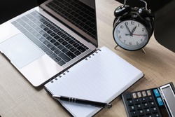 Business accessories on wooden office desk: laptop, pen, book, calculator and alarm clock