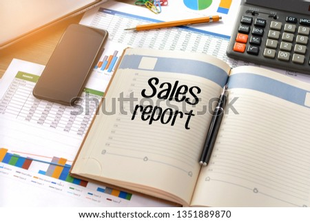 Business accessories, smartphone calculator, laptop, reports and diary with text Sales report