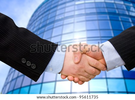 business accounting balance. Handshake with modern skyscrapers as background.