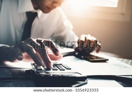 Business accounting, Business man using calculator with computer laptop, budget and loan paper in office.