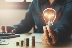 business accounting with saving money with hand holding lightbulb concept financial background