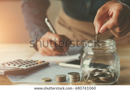 business accounting with saving money with hand putting coins in jug glass concept financial