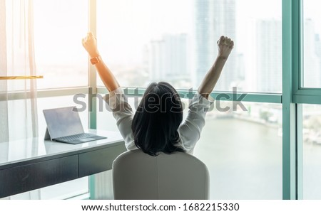 Business achievement concept with happy businesswoman relaxing in office or hotel room, resting and raising fists with ambition looking forward to city building urban scene through glass window Foto stock ©