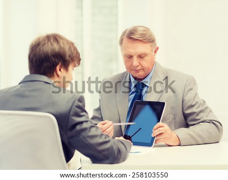 business, advertisement, technology and office concept - older man and young man with tablet pc computer in office