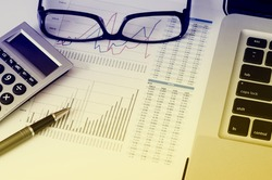 Business Analysis and Report with pen, notebook, glass and calculator