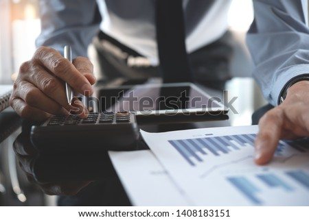 Business analysis, investment and finance concept. Businessman, accountant using calculator to calculate business report, marketing data, financial graph, spreadsheet and digital tablet on office desk
