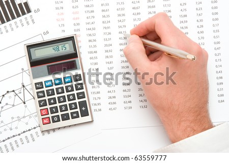 Business analyst - hand with pen; calculator, sheet and graph from top view