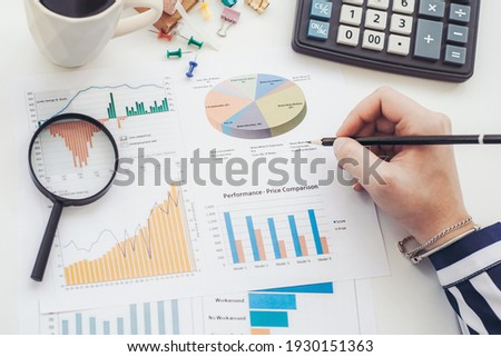 Business analyst working - hand with pen, calculator, coffee, magnifier, worksheet and graph Foto stock ©