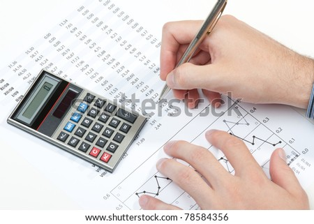 Business analyst working - hand with pen, calculator, sheet and graph