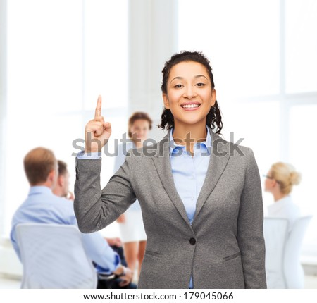 business and advertisement concept - attractive young woman with her finger up at office