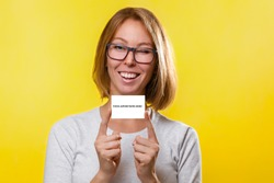 Business and advertising. The young woman the blonde in glasses, holds index fingers both hands Bank card or business card. Yellow background. Copy space and mock up