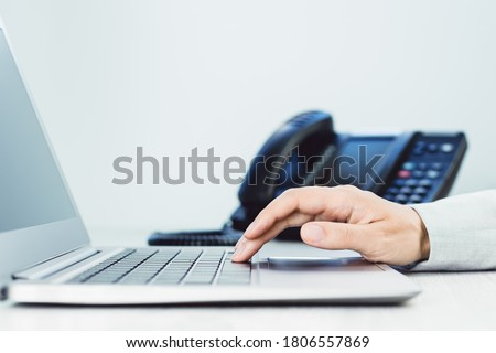 business and communications. Female hand and voip phone in the office. finance graphs. laptop on desk. IP telephony, Cold calling. Audit accounting small business. Induction. copy space