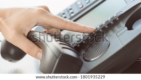 business and communications. Using voip phone in the office, close up of hand with receiver. Conference call, contact us or hotline banner. IP telephony, Telemarketing. Help desk or call centre