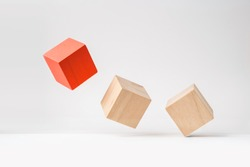 Business and design concept - abstract geometric real wooden cube with surreal layout on white floor background and it's not 3D render. It's the symbol of leadership, teamwork and growth