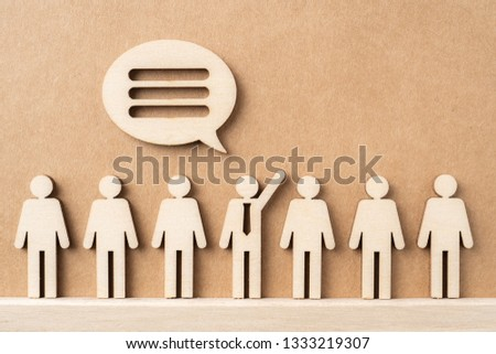 Business and design concept - group of wooden businessman icon with jigsaw dialogue frame on kraft paper. it's conversation, leadership concept #1333219307