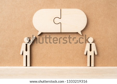 Business and design concept - group of wooden businessman icon with jigsaw dialogue frame on kraft paper. it's conversation, leadership concept #1333219316