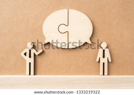 Business and design concept - group of wooden businessman icon with jigsaw dialogue frame on kraft paper. it's conversation, leadership concept #1333219322
