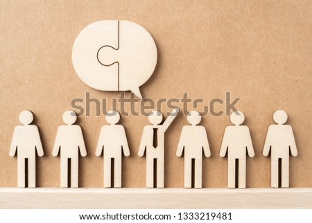 Business and design concept - group of wooden businessman icon with jigsaw dialogue frame on kraft paper. it's conversation, leadership concept #1333219481