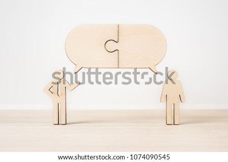 Business and design concept - group of wooden businessman icon with jigsaw dialogue frame on wooden desktop and white background.  it's discussion, leadership concept #1074090545
