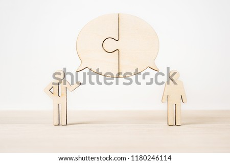 Business and design concept - group of wooden businessman icon with jigsaw dialogue frame on wooden desktop and white background. it's discussion, leadership concept #1180246114