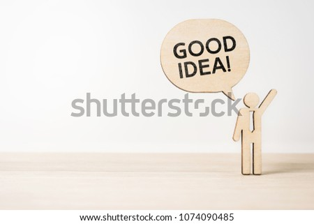"""Business and design concept - wooden businessman icon with dialogue frame """" GOOD IDEA """" on wooden desktop and white background  #1074090485"""