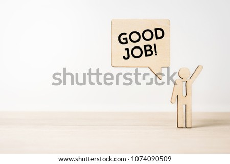 """Business and design concept - wooden businessman icon with dialogue frame """" GOOD JOB """" on wooden desktop and white background  #1074090509"""
