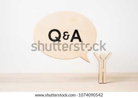 """Business and design concept - wooden businessman icon with dialogue frame """" Q & A """" on wooden desktop and white background  #1074090542"""