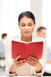 business and education concept - woman reading book in college or office