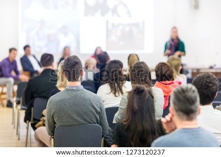 Business and entrepreneurship symposium. Female speaker giving a talk at business meeting. Audience in conference hall. Rear view of unrecognized participant in audience. Copy space on whitescreen. #1273120237