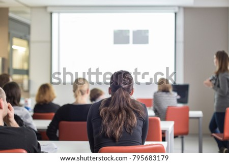 Business and entrepreneurship symposium. Female speaker giving a talk at business meeting. Audience in conference hall. Rear view of unrecognized participant in audience.