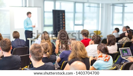 Business and entrepreneurship symposium. Speaker giving a talk at business meeting. Audience in conference hall. Rear view of unrecognized participant in audience.