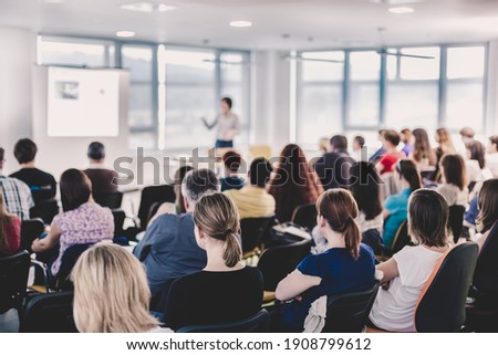 Business and entrepreneurship symposium. Speaker giving a talk at business meeting. Audience in conference hall. Rear view of unrecognized participant in audience. Foto d'archivio ©