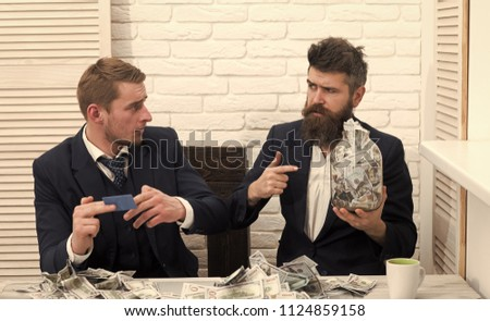 Business and finance. Business partners, businessmen at meeting in office. Bearded boss holds jar full of cash, colleague holds credit card. #1124859158