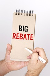 Business and finance concept. A man holds a pen and a bolknot in his hands with the inscription - Big Rebate