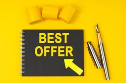 Business and finance concept. On a yellow background lies a pen, a black notebook with the inscription - BEST OFFER