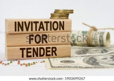 Business and finance concept. On the table are dollars, financial charts and wooden plates on which it is written - INVITATION FOR TENDER Stock photo ©