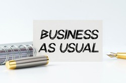 Business and finance concept. On the table is a notebook, a pen and a business card with the inscription - BUSINESS AS USUAL