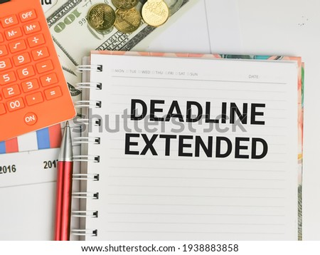 Business and finance concept. Phrase DEADLINE EXTENDED written on notebook with a pen,calculator,coins and fake money. Stock fotó ©