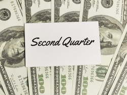 Business and finance concept. Phrase Second Quarter written on white note with fake money.