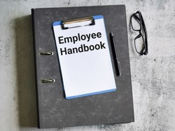 Business and finance concept. Selective focus paper clipboard written employee handbook with pen,ring file and eye glasses.