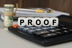 Business and finance concept. There are cubes on the calculator that say - PROOF. Nearby out of focus - dollars, notebook and pen