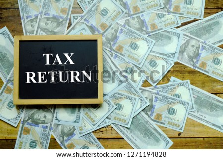 Business and finance concept. Top view of blackboard written with TAX RETURN with dollar banknote at the background. #1271194828